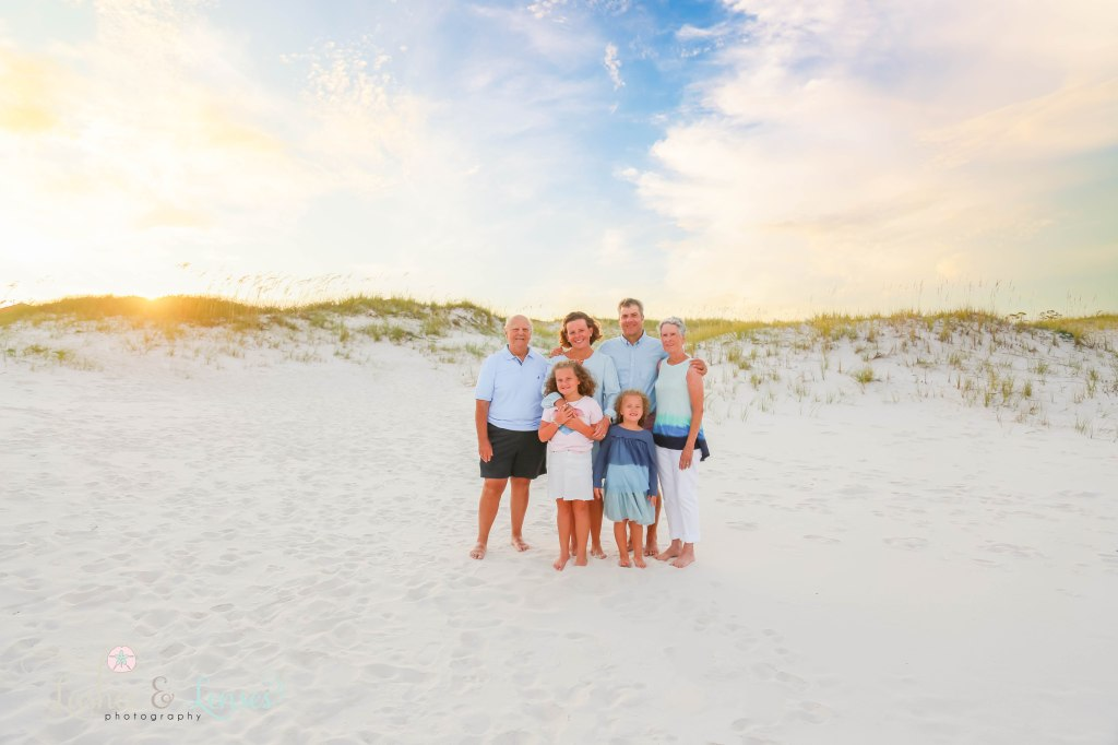 Mom and Dad with their two daughters and grandparents standing with the sunset and sand dunes behind them at Johnsons Beach in Perdido Key Florida