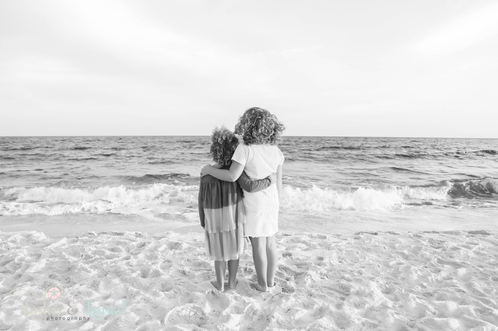 Black and White photo of two sisters hugging each others backs and looking out at the water at Johnsons Beach in Perdido Key Florida