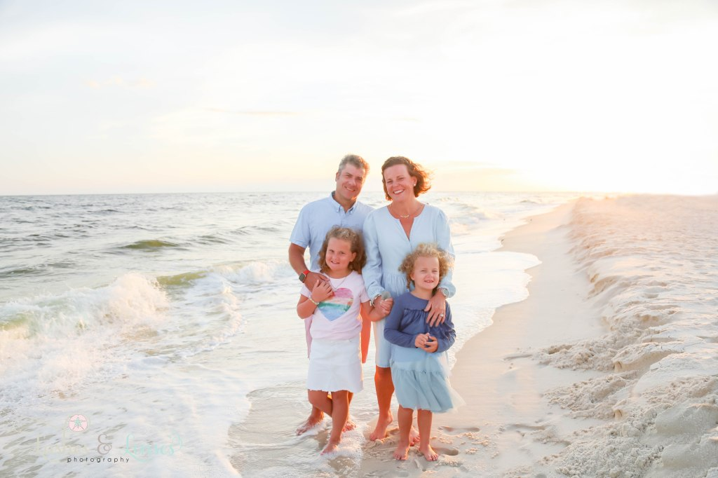 Mom and Dad with their two daughters standing right next to the water at Johnsons Beach in Perdido Key Florida