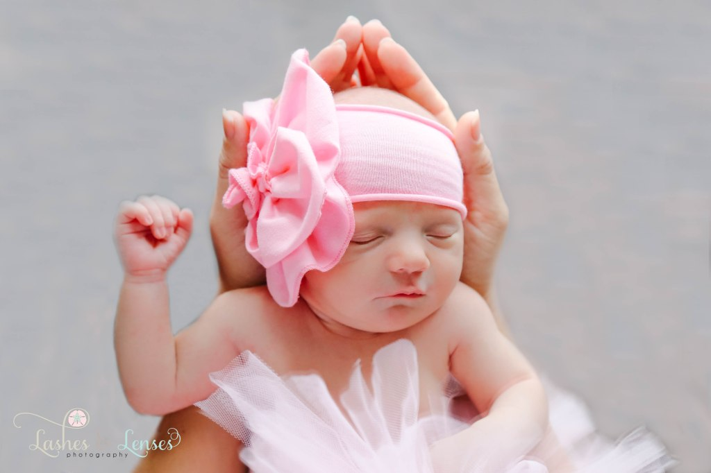 Mom holding her newborn daughter in her hands, baby is wearing a flower headband and a pink tutu photo taken in Pensacola, Florida