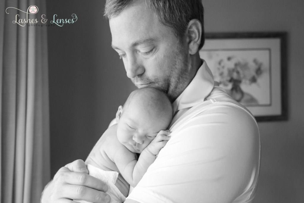 Black and white photo of Dad holding his newborn daughter, photo taken in Pensacola, Florida