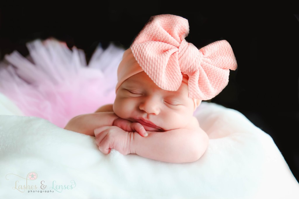 Newborn girl laying on her arms with a light peach bow in her hair and wearing light pink tutu, photo taken in Pensacola, Florida