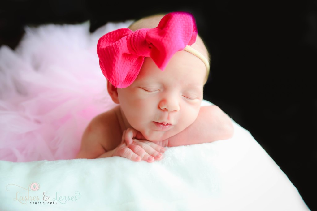 Newborn girl with her head on her hands wearing a pink pink bow and a light pink tutu, photo taken in Pensacola Florida